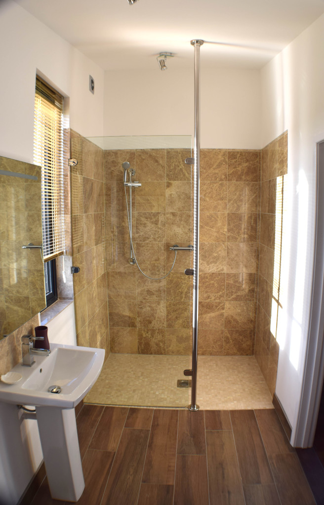 Walk in shower with marble walls