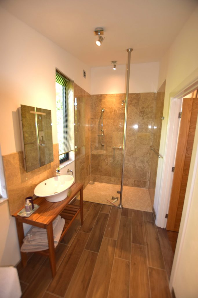 Lodge 1 bathroom, a generous size room with natural stone tiles and a walk in shower.